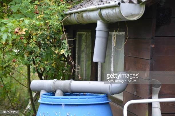 Gray Pipe On Drum By Wooden House