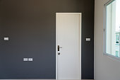 Gray wall decoration of the bedroom with white door closed.