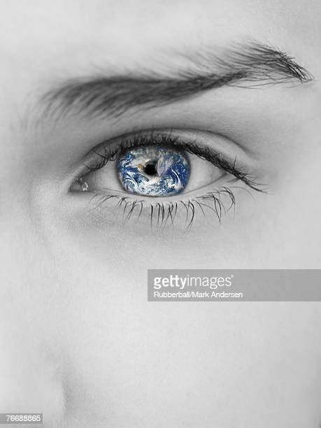 Grayscale close-up of woman's eye with earth reflection