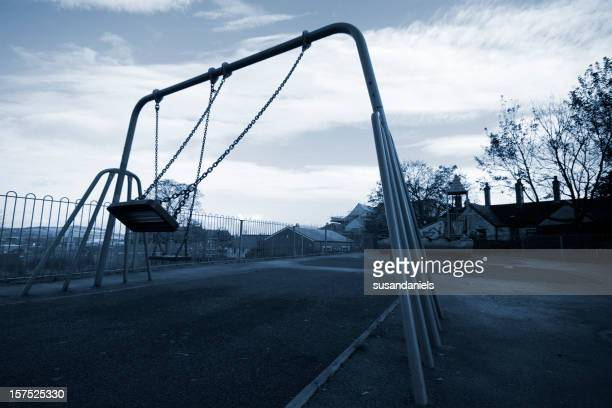 A grayscale playground swing in mid swing