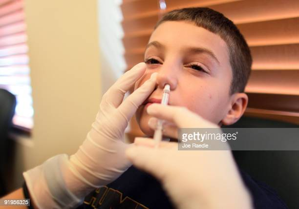 Grayson Handwerker receives a H1N1 nasal flu spray vaccine from medical assistant Mayra Medrano at MD Now Urgent Care Centers on October 16 2009 in...