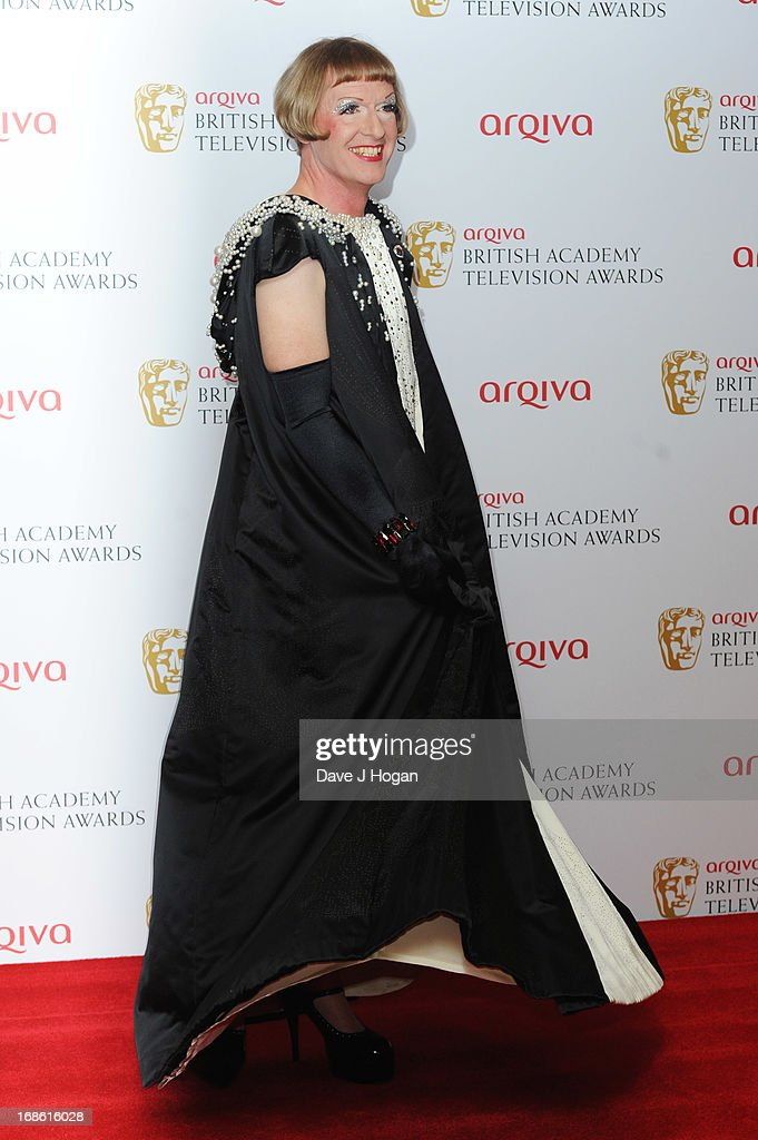 Grayson Perry poses in front of the winners boards at the BAFTA TV Awards 2013 at The Royal Festival Hall on May 12, 2013 in London, England.
