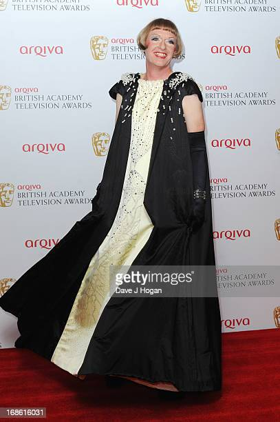 Grayson Perry poses in front of the winners boards at the BAFTA TV Awards 2013 at The Royal Festival Hall on May 12 2013 in London England