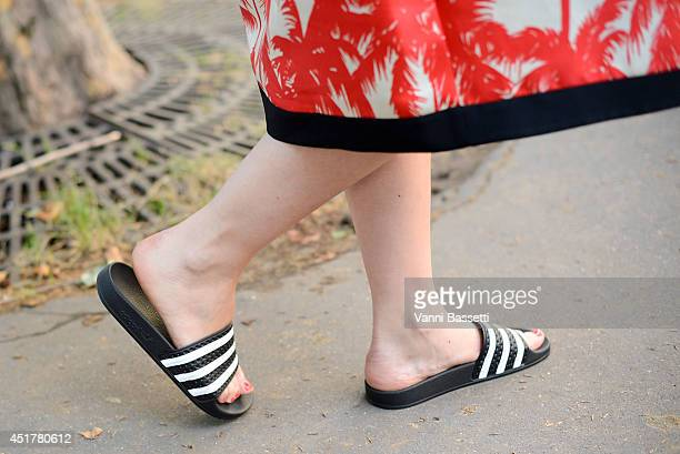 Grazia Germany fashion editor Stephanie Morcinek poses wearing a Fausto Puglisi coat and Adidas slides before Atelier Versace show on July 6 2014 in...