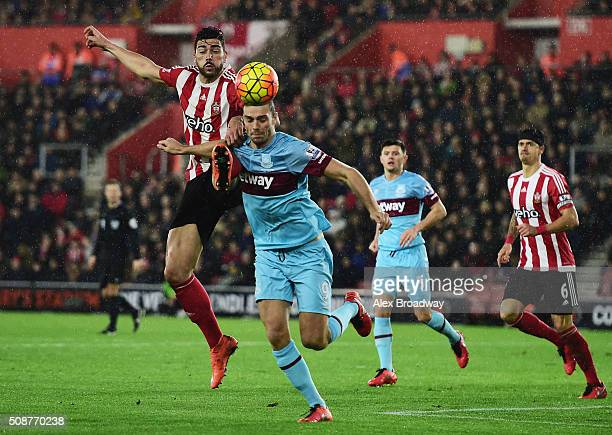 Graziano Pelle of Southampton challenges Andy Carroll of West Ham United during the Barclays Premier League match between Southampton and West Ham...