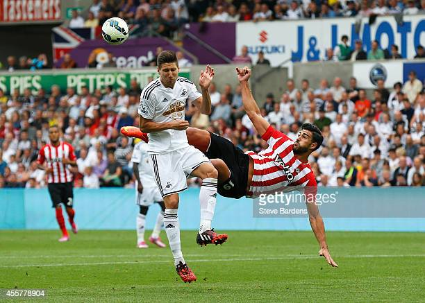 Graziano Pelle of Southampton volleys challenged by Federico Fernandez of Swansea City during the Barclays Premier League match between Swansea City...