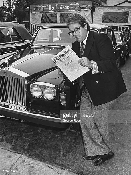 'Grease' film producer Alan Carr leans against his car while reading Daily Variety in front of Los Angeles California restaurant Ma Maison