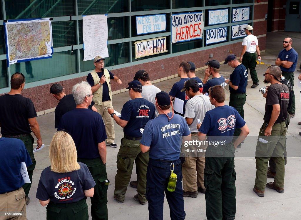 Great Basin National Incident Team 2 Planning Section Chief Steve Jackson leads a night crew briefing for firefighters at the incident command post for the Carpenter 1 fire at Centennial High School where local residents have put up signs of support on July 10, 2013 in Las Vegas, Nevada. More than 25,000 acres have burned since lightning sparked the blaze in Carpenter Canyon on the Pahrump, Nevada side of Mount Charleston on July 1. More than 1,000 firefighters are battling the wildfire which crested the peak of Mount Charleston on July 4, prompting the evacuation of 520 people as it began descending the east side of the mountain, about 35 miles northwest of Las Vegas. The fire is 10% contained and fire officials estimate that they won't have it fully contained until July 19.