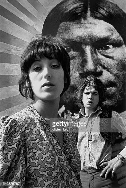 Great Britain England London hippie girl and boy in Chelsea in front of poster with Indian chief