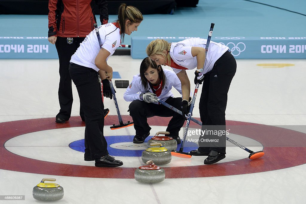 Great Britain skip Eve Muirhead watches as the third Anna Sloan sweeps and the second Vicki Adams looks on during a women's curling qualifier against...