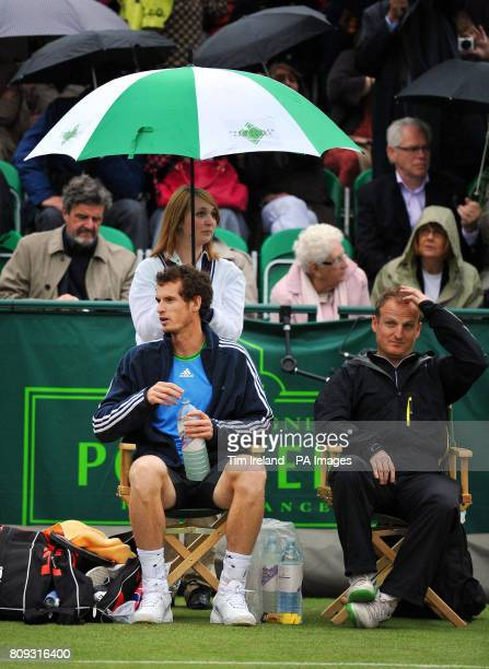 Great Britain's Andy Murray is sheltered by an umbrella during an exhibition match against Serbia's Victor Troicki during The Boodles event at Stoke...