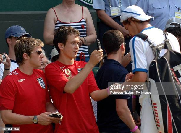 Great Britain's Andy Murray signs autographs for fans following his win over France's Julien Benneteau in the second round of The All England Lawn...
