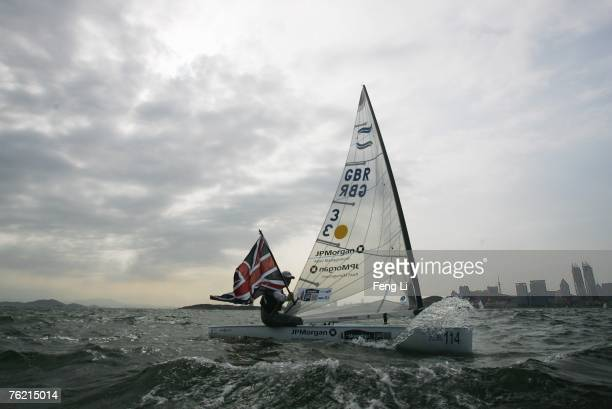 Great Britain's Ben Ainslie hoists the Union Jack after winning gold in the Finn sailing medal race during the Qingdao International Regatta on...