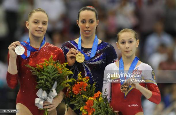 Great Britain's Beth Tweddle celebrates winning gold on the floor with Russia's Anna Myzdrikova and Romania's Diana Maria Chelaru during the European...