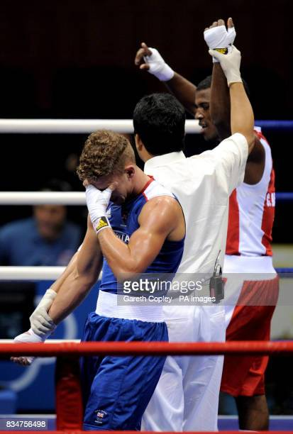 Great Britain's Billy Joe Saunders holds his head after being beat by Cuba's Carlos Banteaux Suarez during their second round Welterweight bout at...