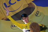 Great Britain's Christopher Froome celebrates his overall leader yellow jersey on the podium at the end of the 160 km fifteenth stage of the 103rd...