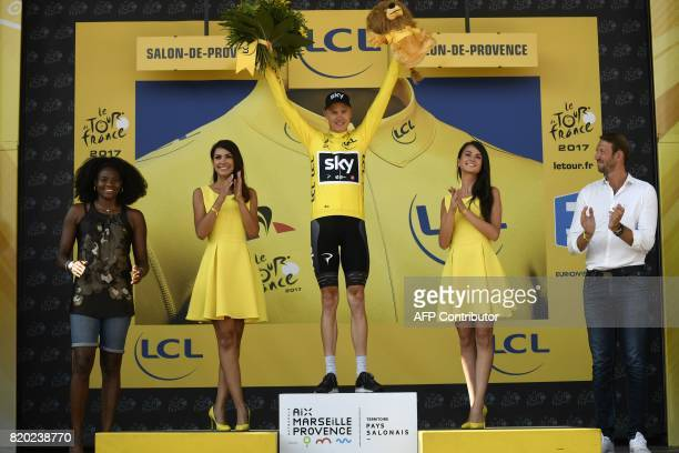 Great Britain's Christopher Froome celebrates his overall leader yellow jersey on the podium as French former olympic champion Alain Bernard and...