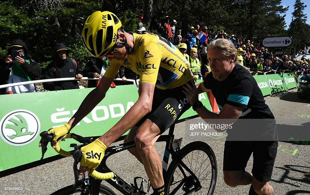 Great Britain's Christopher Froome is helped as he gets on a replacement bike after falling during the 178 km twelvelth stage of the 103rd edition of the Tour de France cycling race on July 14, 2016 between Montpellier and Chalet-Reynard. / AFP / jeff pachoud