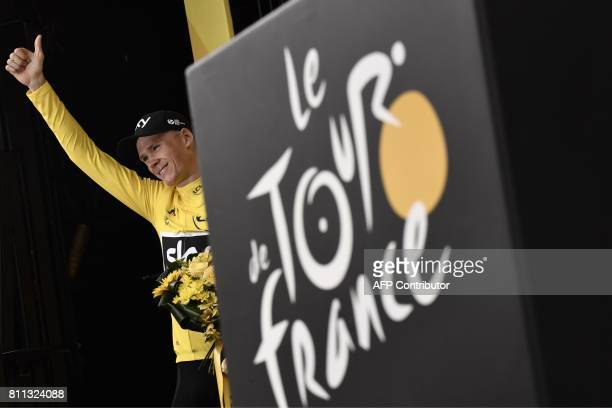 Great Britain's Christopher Froome thumbs up as he celebrates his overall leader yellow jersey on the podium at the end of the 1815 km ninth stage of...