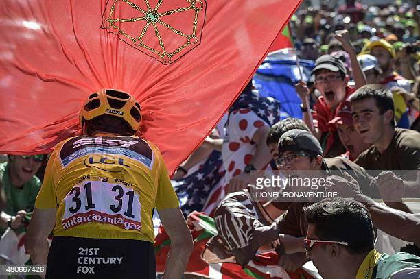 Great Britain's Christopher Froome wearing the overall leader's yellow jersey rides in the last hill despite of a flag wave by supporters during the...