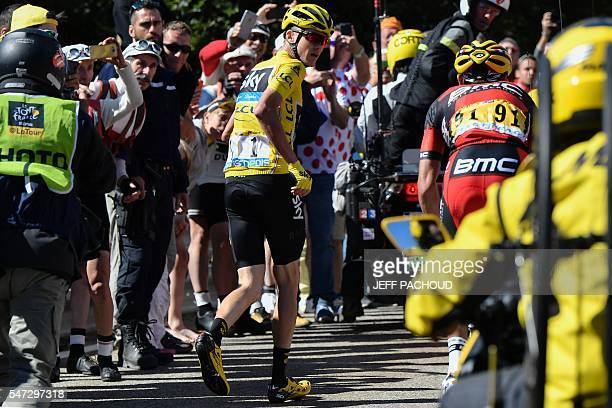 Great Britain's Christopher Froome wearing the overall leader's yellow jersey runs to get another bike after falling during the 178 km twelvelth...