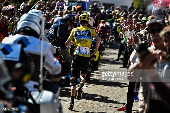 TOPSHOT Great Britain's Christopher Froome wearing the overall leader's yellow jersey runs to get a replacement bike following a fall during the 178...