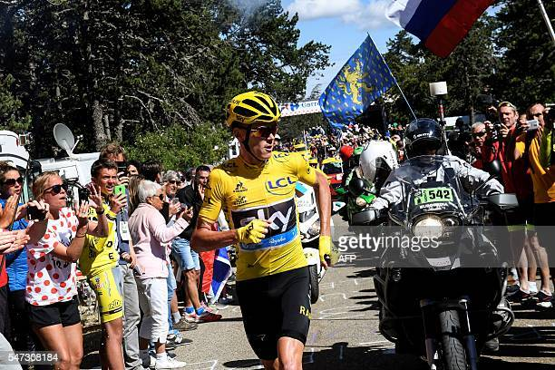 Great Britain's Christopher Froome wearing the overall leader's yellow jersey runs to get a replacement bike after falling during the 178 km...