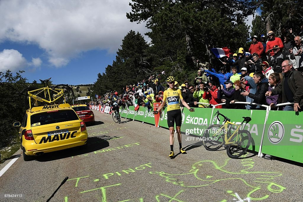 Great Britain's Christopher Froome (C), wearing the overall leader's yellow jersey, gestures as he waits for a replacement bike next to a dysfunctional one following a fall during the 178 km twelvelth stage of the 103rd edition of the Tour de France cycling race on July 14, 2016 between Montpellier and Chalet-Reynard. / AFP / jeff pachoud