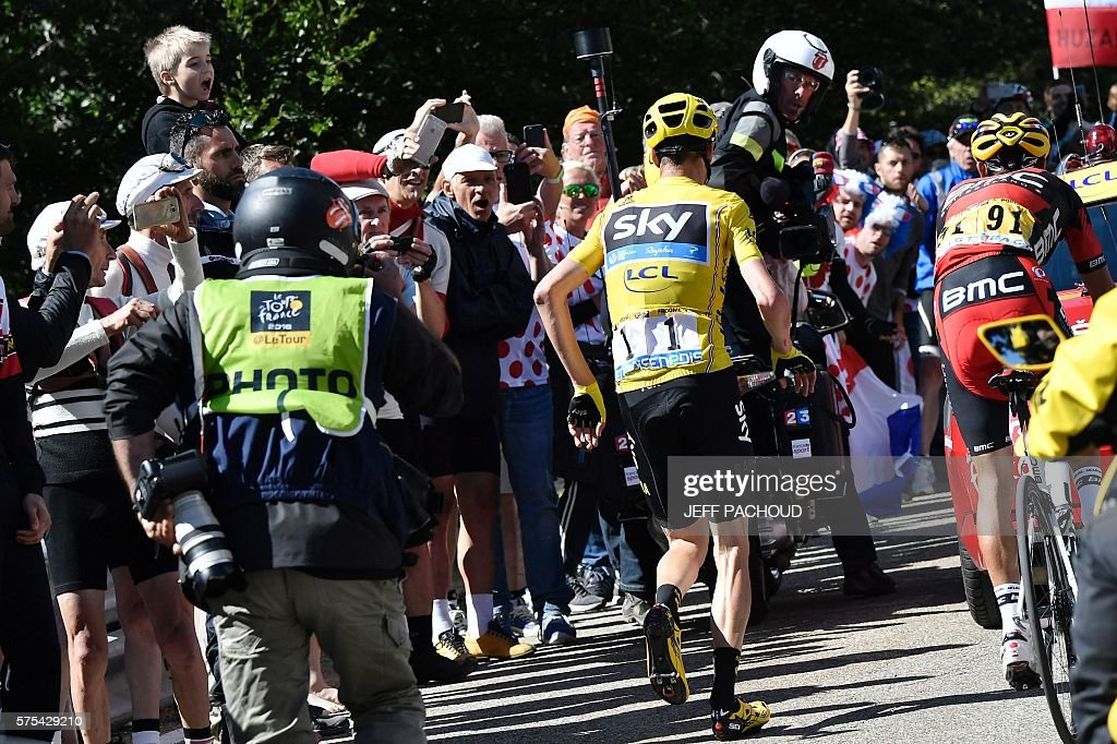 Great Britain's Christopher Froome, wearing the overall leader's yellow jersey, runs to get another bike after falling during the 178 km twelvelth stage of the 103rd edition of the Tour de France cycling race on July 14, 2016 between Montpellier and Chalet-Reynard. / AFP / JEFF