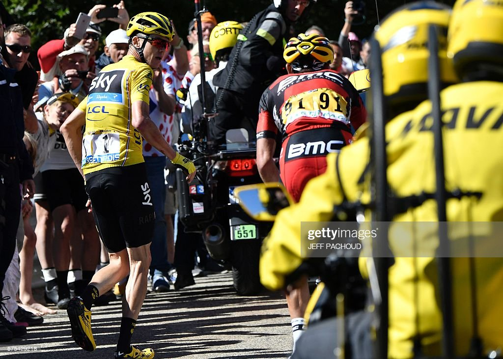 Great Britain's Christopher Froome, wearing the overall leader's yellow jersey, looks behind him as he runs to get another bike after falling during the 178 km twelvelth stage of the 103rd edition of the Tour de France cycling race on July 14, 2016 between Montpellier and Chalet-Reynard. / AFP / JEFF