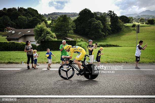 TOPSHOT Great Britain's Christopher Froome wearing the overall leader's yellow jersey rides past fans during the 17 km individual timetrial the...