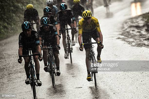 Great Britain's Christopher Froome wearing the overall leader's yellow jersey rides in the rain with his teammates during the 1465 km twentieth stage...