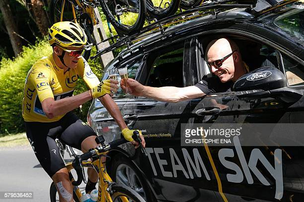 Great Britain's Christopher Froome wearing the overall leader's yellow jersey and Team Sky director Sir Dave Brailsford drink a glass of champagne at...
