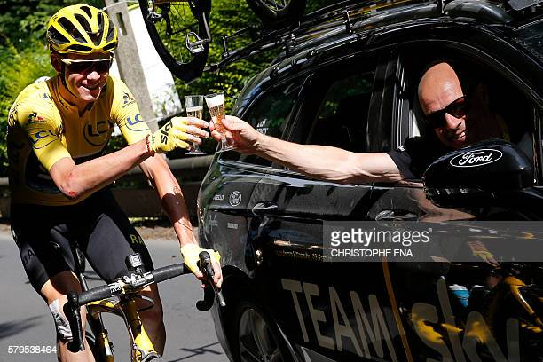 TOPSHOT Great Britain's Christopher Froome wearing the overall leader's yellow jersey and Team Sky director Sir Dave Brailsford drink a glass of...