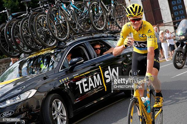 Great Britain's Christopher Froome wearing the overall leader's yellow jersey drinks a glass of champagne at the start of the 113 km twentyfirst and...