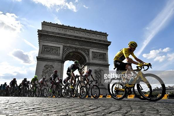 TOPSHOT Great Britain's Christopher Froome wearing the overall leader's yellow jersey rides in the pack in front of the Arc de Triomphe during the...