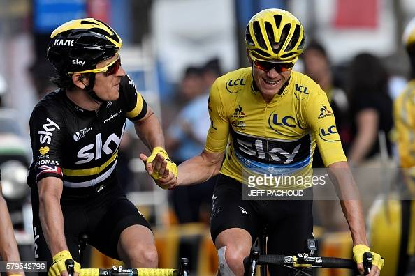 Great Britain's Christopher Froome wearing the overall leader's yellow jersey holds hands with Great Britain's Geraint Thomas as they cross the...