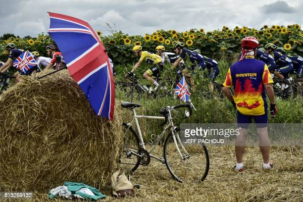 Great Britain's Christopher Froome wearing the overall leader's yellow jersey rides past a supporter cheering along the road next to UK Union Jack...