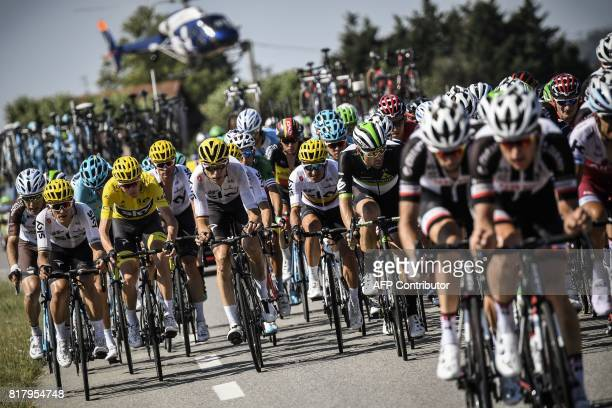 Great Britain's Christopher Froome wearing the overall leader's yellow jersey rides in the pack with his teammates Poland's Michal Kwiatkowski...