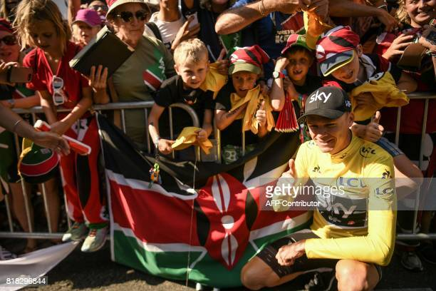 Great Britain's Christopher Froome wearing the overall leader's yellow jersey poses with children standing behind a flag of Kenya at the end of the...