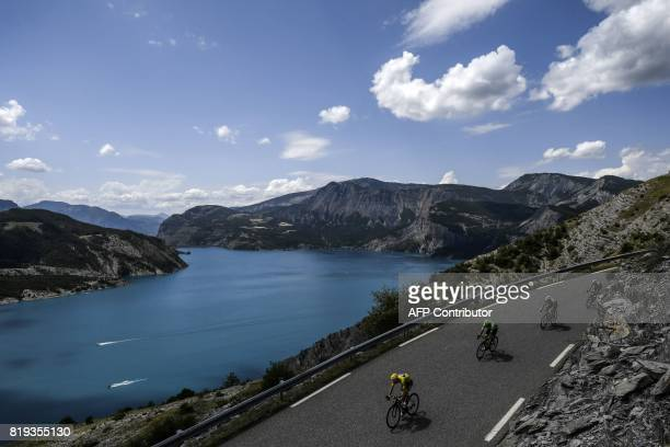 TOPSHOT Great Britain's Christopher Froome wearing the overall leader's yellow jersey rides past a lake during the 1795 km eighteenth stage of the...