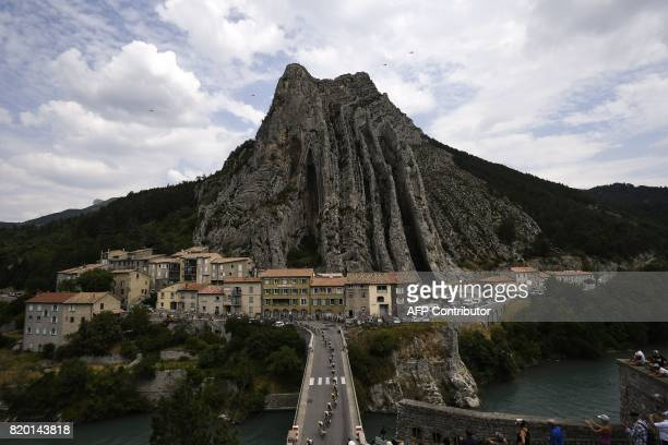 Great Britain's Christopher Froome wearing the overall leader's yellow jersey rides in the pack on a bridge in front of the Rocher de la Baume in...