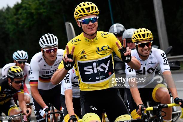 Great Britain's Christopher Froome wearing the overall leader's yellow jersey flashes victory signs next to his teammate Spain's Mikel Landa during...
