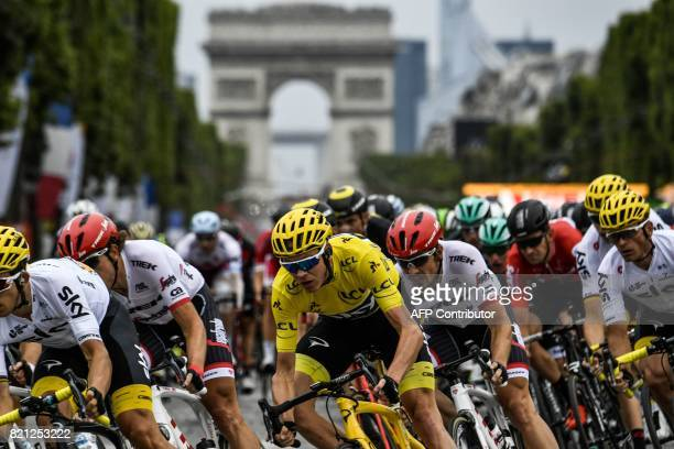 TOPSHOT Great Britain's Christopher Froome wearing the overall leader's yellow jersey rides on the ChampsElysees avenue with the Arc de Triomphe in...