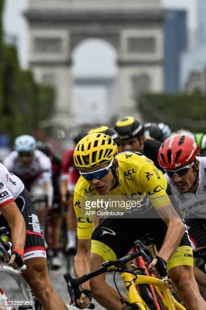 Great Britain's Christopher Froome wearing the overall leader's yellow jersey and Germany's John Degenkolb ride on the ChampsElysees avenue with the...