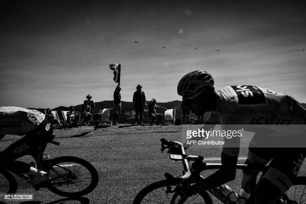 Great Britain's Christopher Froome wearing the overall leader's yellow jersey rides past supporters during the 165 km sixteenth stage of the 104th...