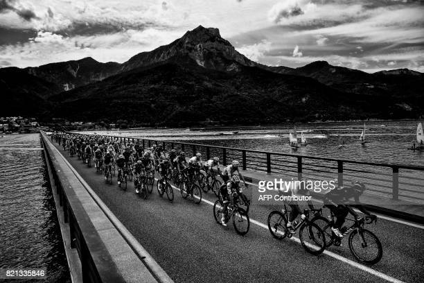 Great Britain's Christopher Froome wearing the overall leader's yellow jersey rides in the pack on a bridge past a lake during the 2225 km nineteenth...