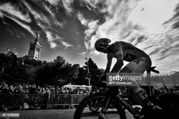 Great Britain's Christopher Froome wearing the overall leader's yellow jersey rides past the NotreDame de la Garde basilica as he competes in a 225...