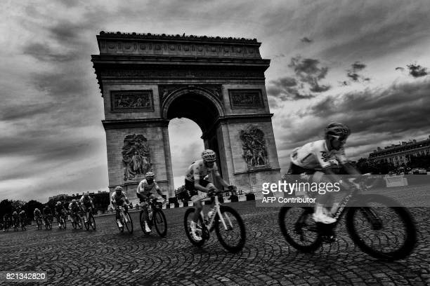 Great Britain's Christopher Froome wearing the overall leader's yellow jersey rides past the Arc de Triomphe during the 103 km twentyfirst and last...