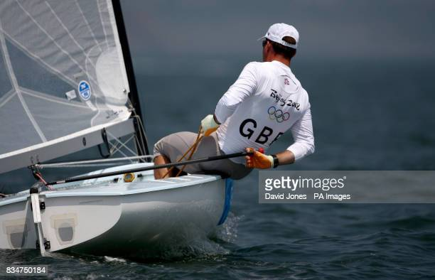Great Britain's Finn sailor Ben Ainslie steers with his hand behind his back on the windward leg of the first day of racing in Qingdao during the...